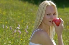 Austria, Salzburger Land, Altenmarkt, Woman sitting in meadow, holding apple, - stock photo