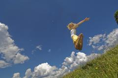 Austria, Salzburger Land, Altenmarkt, Young woman jumping in meadow, smiling Stock Photos