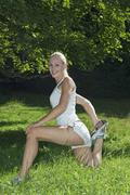 Austria, Salzburger Land, Young woman stretching leg, smiling - stock photo