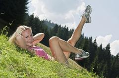 Austria, Salzburger Land, Young woman doing sit ups, smiling Stock Photos