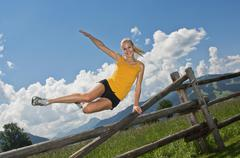 Stock Photo of Austria, Salzburger Land, Young woman jumping over fence