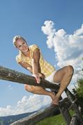 Stock Photo of Austria, Salzburger Land, Young woman sitting on fence, low angle view
