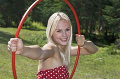 Austria, Salzburger Land, Young woman holding a hula hoop, smiling - stock photo