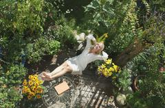 Austria, Salzburger Land, Young woman in garden, relaxing, elevated view Stock Photos
