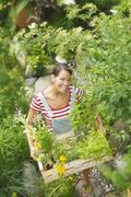 Austria, Salzburger Land, Woman carrying wooden box with plants, elevated view - stock photo