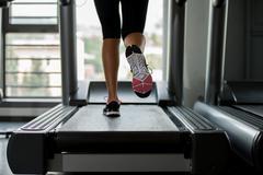 Girl running on treadmill Stock Photos