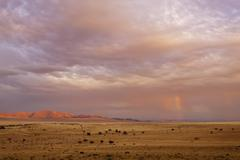 Africa, Namibia, Namib Desert, View of rainbow over gondwana sperrgebiet rand - stock photo