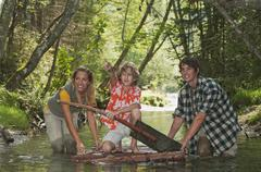 Austria, Salzburger Land, Boy kneeling on timber raft, Parents wading in creek - stock photo