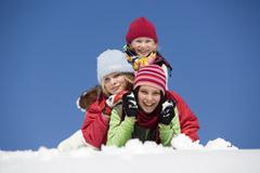 Austria, girls (6-17) lying on snow, smiling, portrait - stock photo