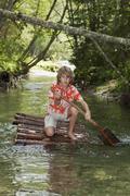 Austria, Salzburger Land, Boy on timber raft, paddling Stock Photos