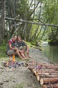 Austria, Salzburger Land, Couple sitting at campfire - stock photo