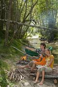 Austria, Salzburger Land, Family sitting at campfire - stock photo