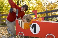 Austria, Salzburger Land, Young man fixing soapbox car, boy (12-13)  watching Stock Photos