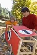 Austria, Salzburger Land, Man and boy (12-13) looking at soapbox car Stock Photos