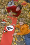 Austria, Salzburger Land, Man and boy (12-13) painting soapbox car element, - stock photo