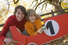 Austria, Salzburger Land, Man and boy (12-13) painting soapbox, smiling - stock photo