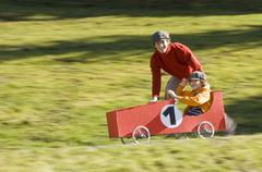 Austria, Salzburger Land, Man and boy (12-13)  with soapbox car, having fun Stock Photos
