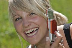 Austria, Salzburger Land, Altenmarkt, Young woman using mobile phone, laughing, Stock Photos