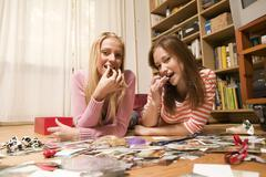 Two girls lying on floor, looking to camera Stock Photos