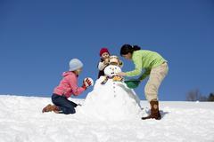 Austria, girls (6-17) making snowman, low angle view - stock photo