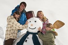 Austria, Salzburger Land, Altenmarkt, Family standing by snowman, smiling, - stock photo