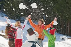 Austria, Salzburger Land, Altenmarkt, Family standing by snowman, throwing snow - stock photo