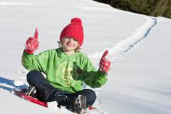 Stock Photo of Austria, Salzburger Land, Altenmarkt, Boy (6-7) on sled, thumbs up, portrait