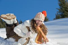 Austria, Salzburger Land, Altenmarkt, Girl (10-11) on sled, smiling, portrait Stock Photos