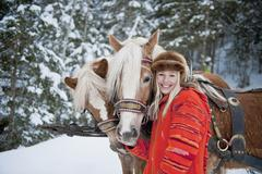 Austria, Salzburger Land, Young woman standing beside horses, smiling, portrait Stock Photos