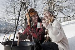 Austria, Salzburger Land, Couple cooking on campfire - stock photo