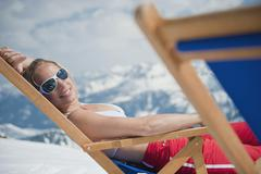 Austria, Salzburger Land, Young woman lying in deck chair, smiling, portrait Stock Photos