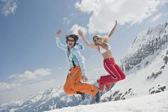 Stock Photo of Austria, Salzburger Land, Young couple jumping in air, laughing, portrait