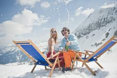 Austria, Salzburger Land, Young couple celebrating with champagne, laughing, - stock photo