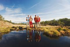 Austria, Salzburger Land, Hikers standing near lake - stock photo