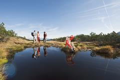 Austria, Salzburger Land, Four hikers near lake Stock Photos