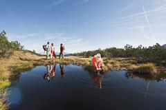 Stock Photo of Austria, Salzburger Land, Four hikers, woman kneeling on the lakefront