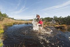 Austria, Salzburger Land, Bikers by lake, man splashing water, laughing, Stock Photos