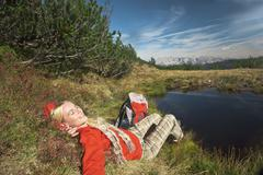 Austria, Salzburger Land, Woman relaxing near lake Stock Photos