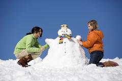 Stock Photo of Austria, girls (12-17) making snowman, side view