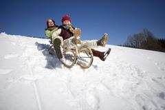 Austria, girls (6-17) sledging on snow covered slope, smiling, low angle view Stock Photos