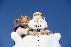 Austria, girl (6-7) hugging snowman, smiling, close-up, portrait Stock Photos