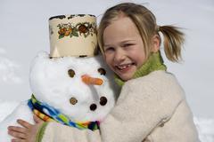 Stock Photo of Austria, girl (6-7) hugging snowman, smiling, close-up, portrait