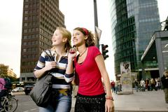 Two girl friends strolling in city Stock Photos