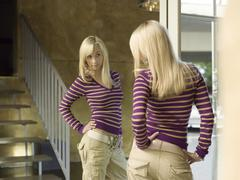Young woman viewing herself in mirror Stock Photos