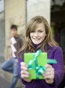 Young woman holding gift, man leaning in background Stock Photos
