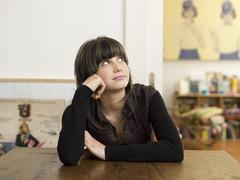 Young woman sitting on table, thinking Stock Photos
