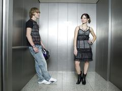 Young couple standing in lift Stock Photos