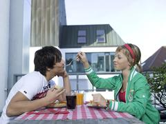 Young woman feeding young man on balcony Stock Photos