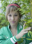 young woman standing by bush, portrait - stock photo