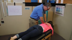 Chiropractor Adjust Patients Back - Wide Shot - stock footage
